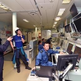 操縦室の説明をする上谷さん(左)