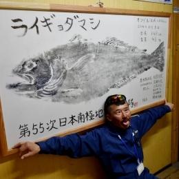 昭和基地の管理棟に飾られているライギョダマシの魚拓と一緒に写る小林隊員