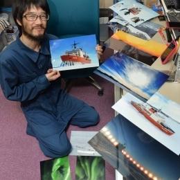 南極で撮影した写真を持つ畑野さん