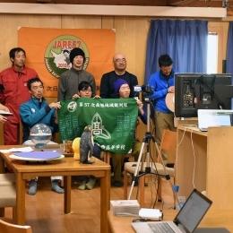 隊員の名前が書かれた旗を持つ南極授業関係者