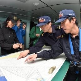 地図上の南磁極を指差す「しらせ」の石井さんと勅使河原さん(右から)