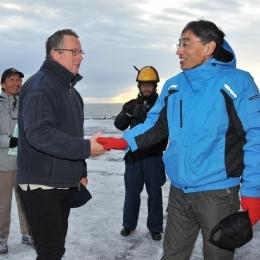 門倉昭隊長(右)と握手する豪モーソン基地のジョン・レーベン隊長(6日午前7時すぎ、日本時間午前11時すぎ、豪モーソン基地沖で)