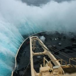 波の上に乗り上げ、船体の周りに大きな水柱が上がる