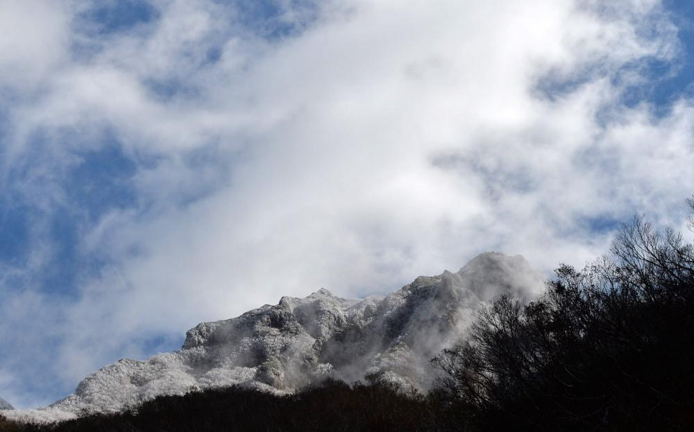 斜里岳。下二股付近(標高800メートルあたり)からガスが晴れた雪化粧のピークを望む