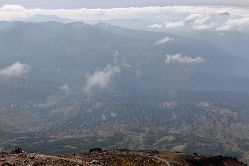 旭岳山頂から南方の眺め。今回はモヤがかかり視界良好ではなかった。遠くにトムラウシ山が見える。