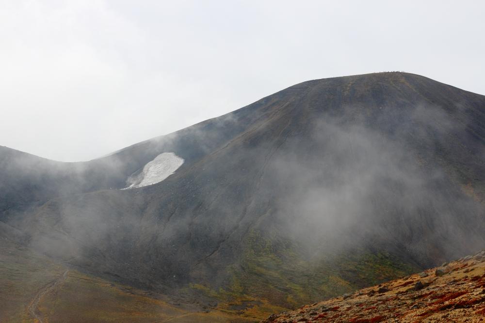 熊ヶ岳に至る途中から見た旭岳。頂上と雪渓付近に人が見える。私はいつもこの勾配で滑落する。