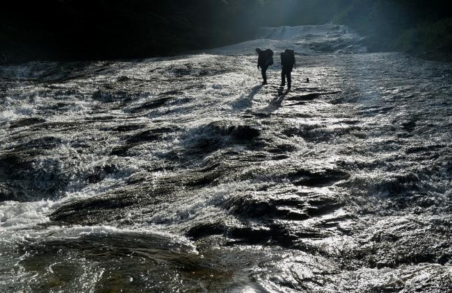 朝日で輝く「滝の瀬十三丁」。クワウンナイ川の最大のヤマ場で、川幅いっぱいに岩盤をはうように流れる「滑(ナメ)」が1キロ以上続く