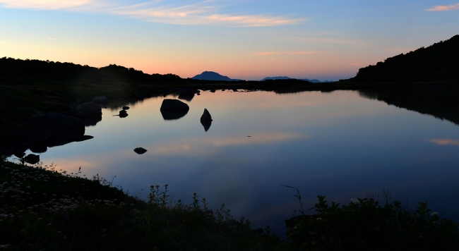 キャンプ指定地になっているヒサゴ沼。起床してすぐにテントを出ると水面に映る朝焼けが目に飛び込んできた